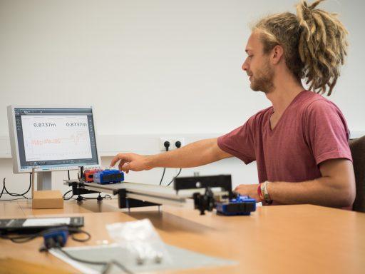 Ein Student misst bei einem physikalischen Versuch mit zwei aufeinander zufahrenden Wagen kinetische Energie.