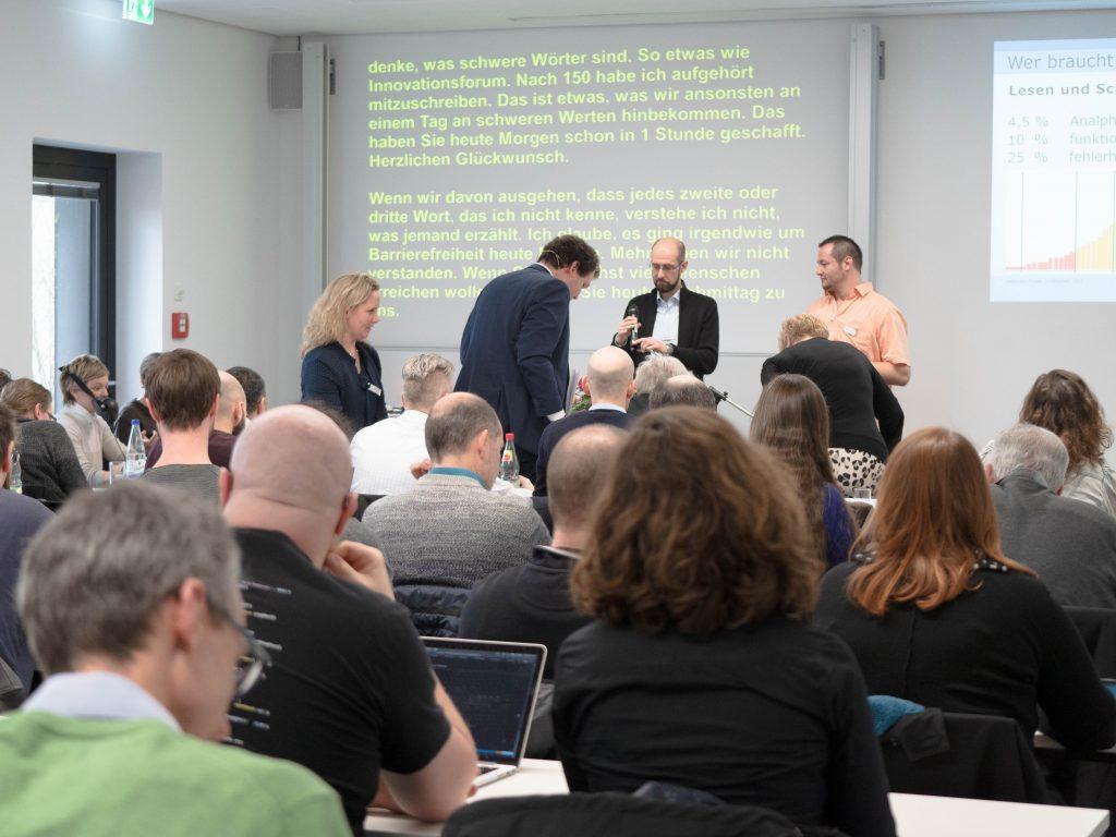 Andreas Deitmer und Dr. Sarah Voß-Nakkour geben den Referenten des Workshops Leichte Sprache gemeinsam am Redner*innenpult ein Dankeschön.