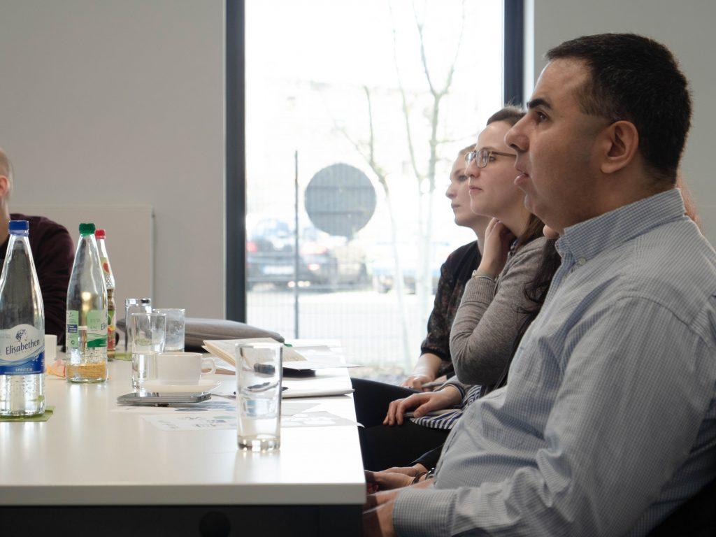 Drei Teilnehmende am Tisch des 2. Vernetzungstreffens.