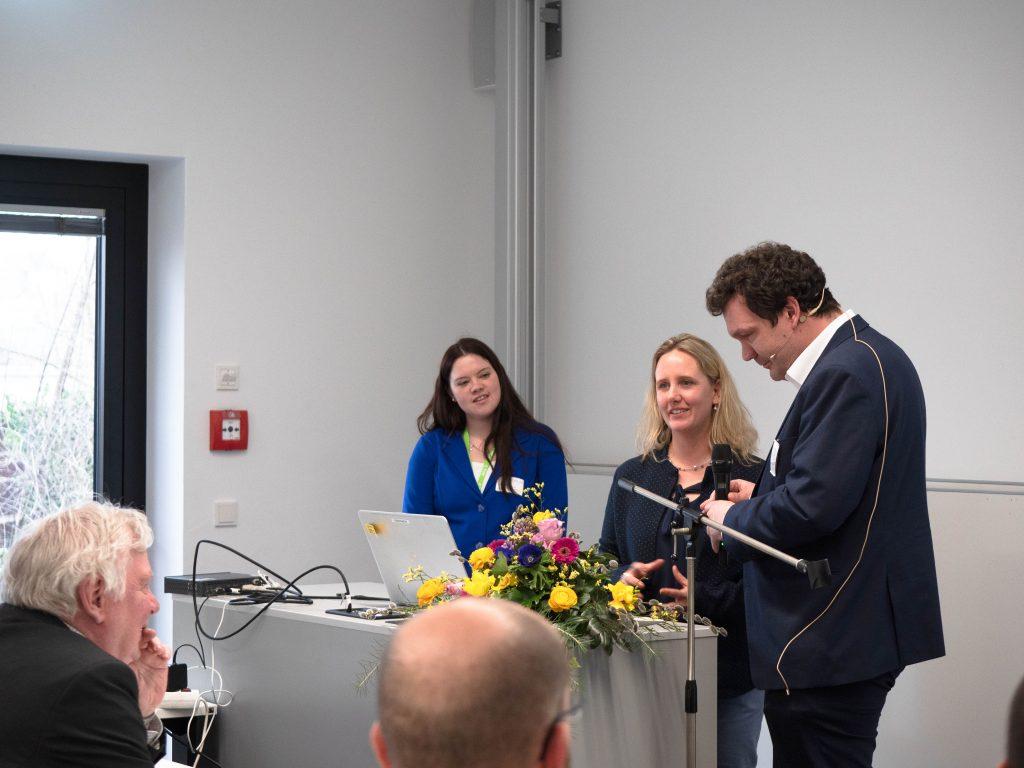 Andreas Deitmer und Dr. Sarah Voß-Nakkour präsentieren gemeinsam am Redner*innenpult den Zwischenstand.