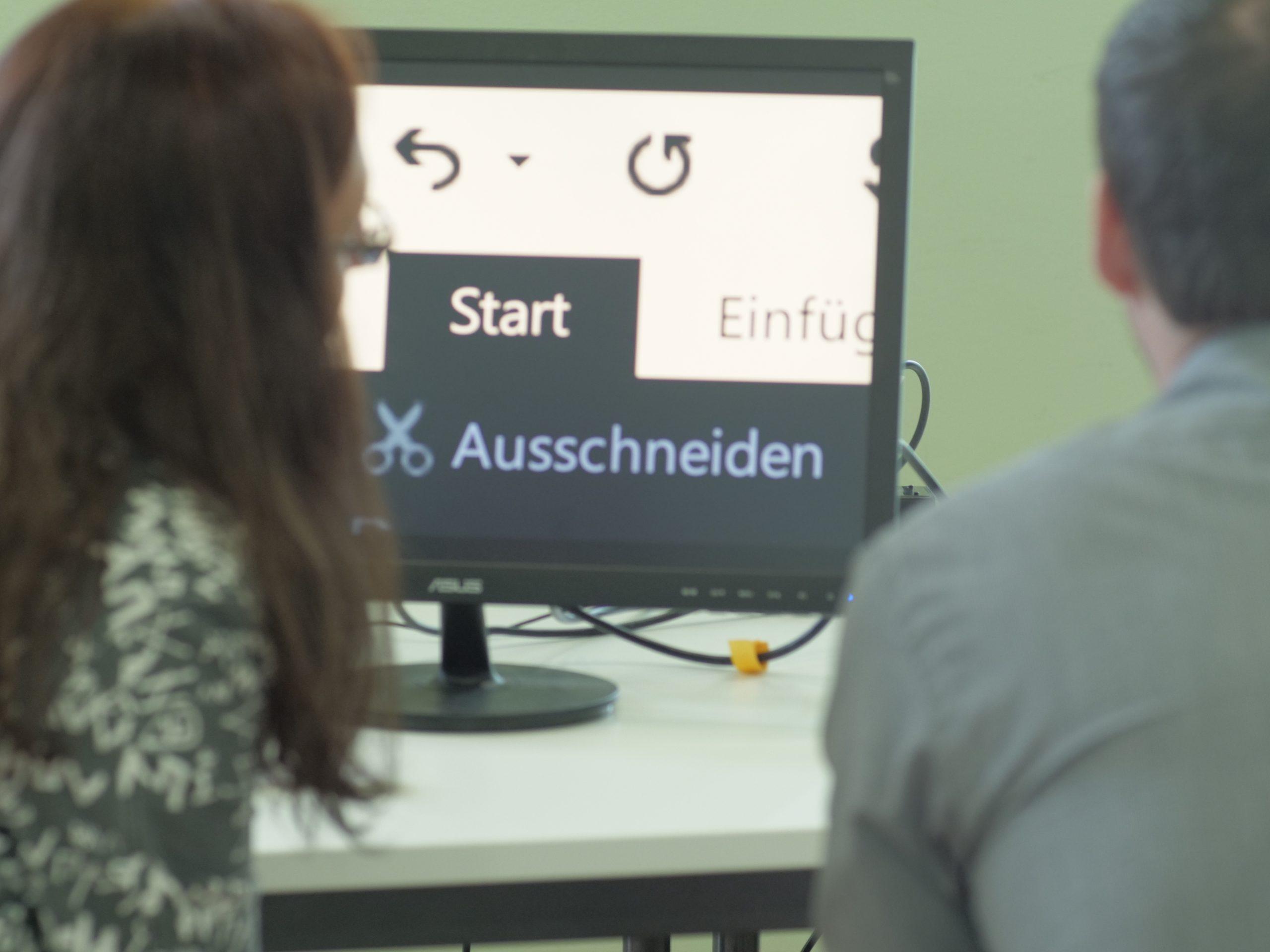 Teilnehmende betrachten einen Desktopbildschirm mit aktivierter Bildschirmlupe