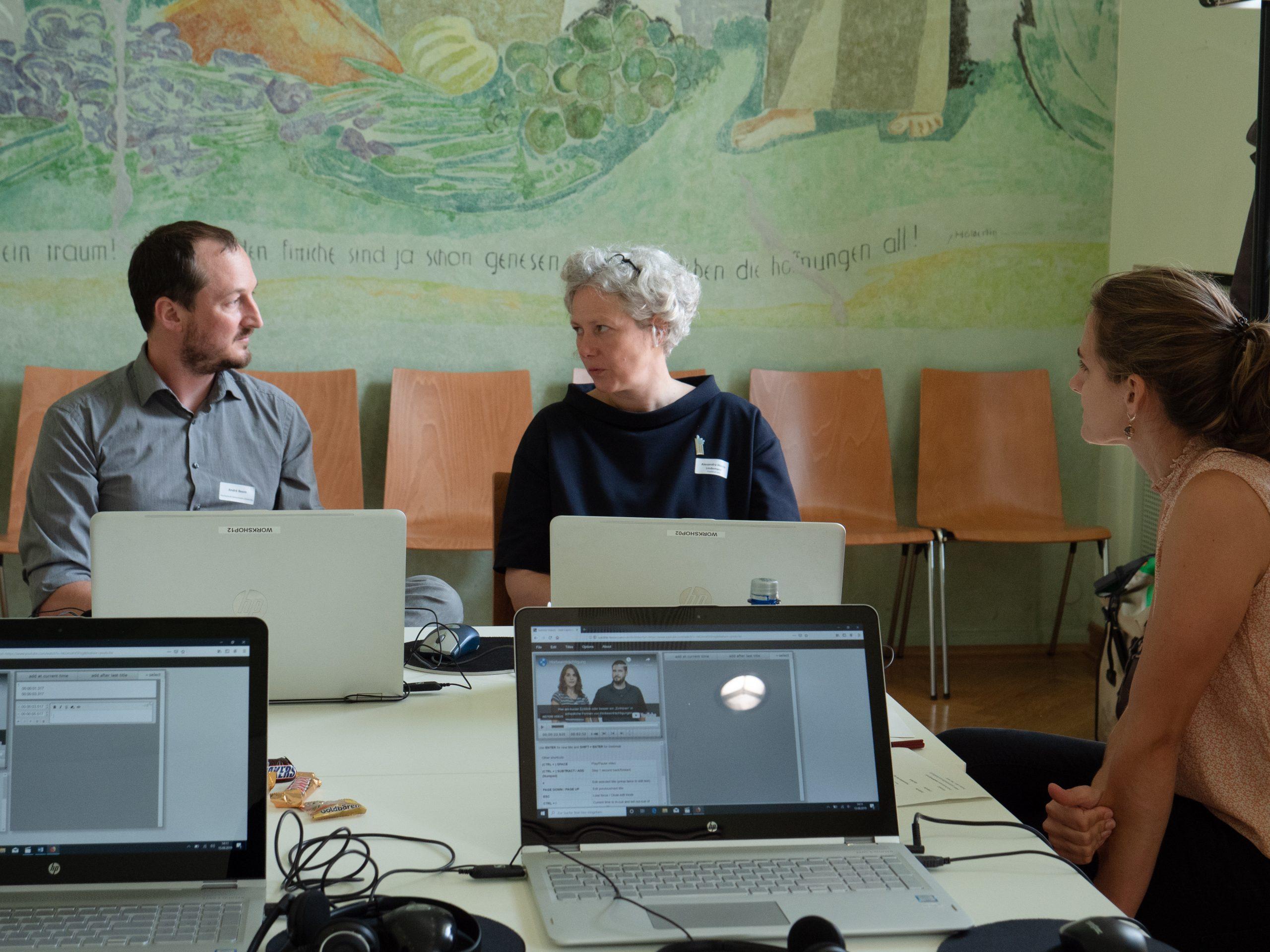Teilnehmende unterhalten sich an den Workshop-Arbeitsplätzen.