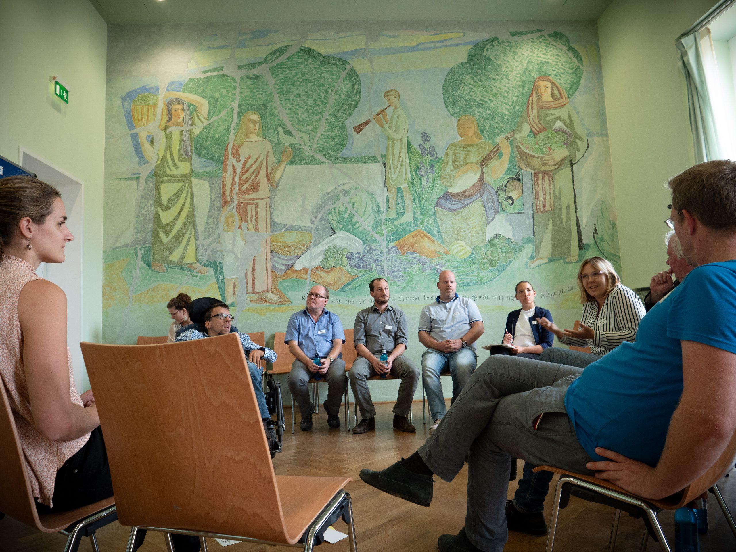 Teilnehmende sitzen im Stuhlkreis